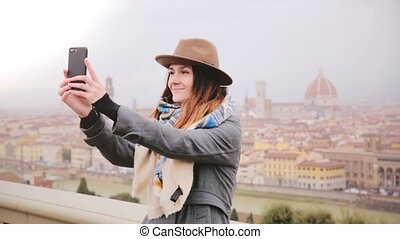 Happy smiling tourist girl taking smartphone selfie photo at...