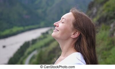 Happy smiling tourist woman enjoying the view on top of the mountain. slow motion