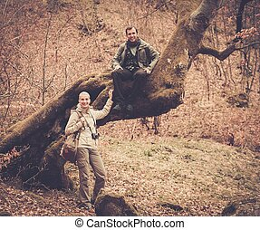 Happy smiling travelers couple in a forest