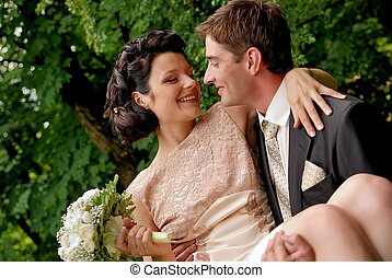 Happy smiling wedding couple outdoors. Man is holding woman...