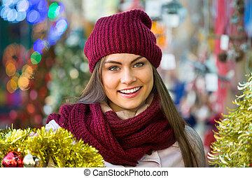 Happy smiling woman choosing Christmas decoration