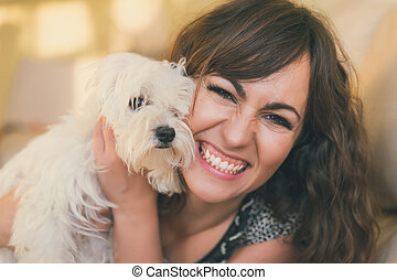 Happy smiling woman cuddling her pet dog