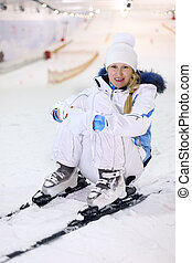 Happy smiling woman dressed in white sports clothes sits on ski in indoor ski