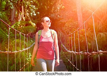 Happy smiling woman hiker crossing suspension bridge in sunlight.