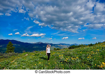 Happy smiling woman hiking in meadows.
