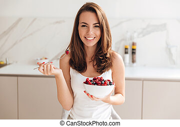 Happy smiling woman holding bowl with fresh berries while...