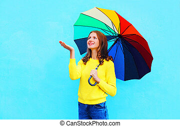 Happy smiling woman holding colorful umbrella in autumn day looking up over colorful blue background wearing yellow knitted sweater