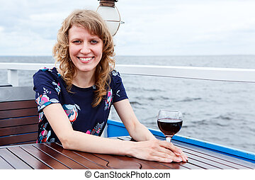 Happy smiling woman in dress with wine glass sitting at the table