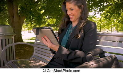 Happy smiling woman in her 30s holding touchpad digital tablet outside