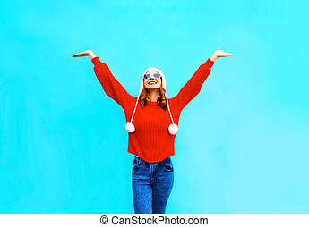 Happy smiling woman in red knitted sweater and hat on a blue background