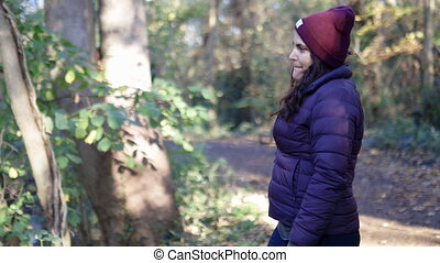 Happy woman wearing knitted hat smiling and joyfully throwing a small stick in a forest. Vibrant brunette woman in forest tossing a stick. Adventurous day in nature