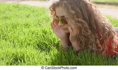 Happy smiling woman lying on green grass enjoying life,...