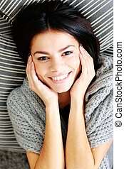 Happy smiling woman lying on the floor with pillows. View from above