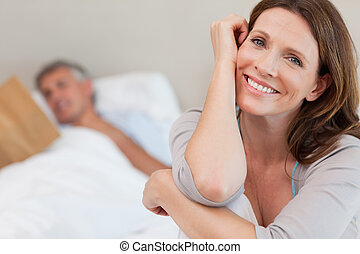 Happy smiling woman on bed with husband reading behind her -...