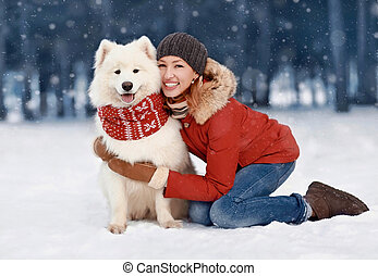 Happy smiling woman owner embracing white Samoyed dog outdoors wearing red scarf while sitting on snow in winter snowy day over flying snowflakes