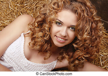 Happy smiling woman portrait with healthy curly hairs on natural harvest background