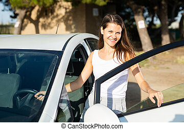 Happy smiling woman posing next to new car on the street