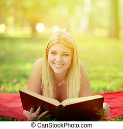 Happy smiling woman reading book in park