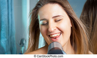 Happy smiling woman singing with hair dryer at bathroom