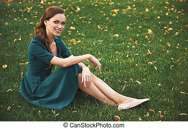 happy smiling woman sitting on a green grass