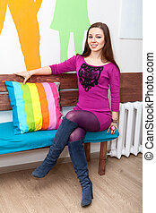 Happy smiling woman sitting on bench in room