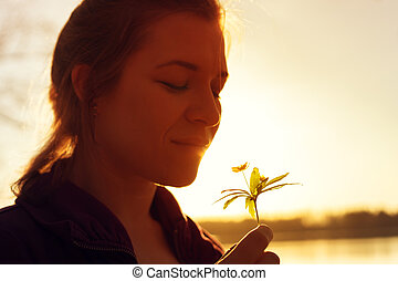 Happy smiling woman smelling forest flower