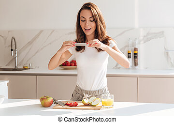 Happy smiling woman taking a picture of fruit slices on a...