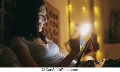 Happy smiling woman using tablet computer for sharing social media lying in bed at home at night