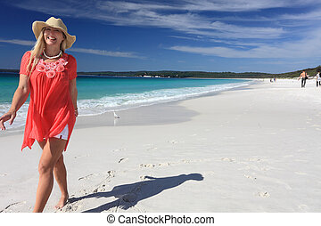 Happy smiling woman walking along beautiful sandy beach -...