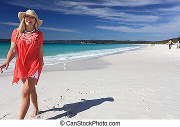 Happy smiling woman walking along beautiful sandy beach - ...