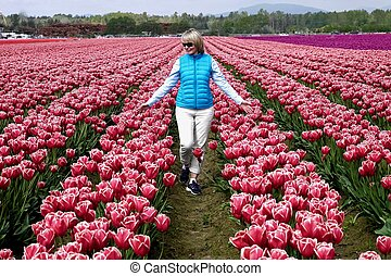 Happy smiling woman walking through colourful tulip fields.