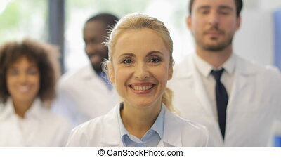 Happy Smiling Woman Walking With Team Of Doctors In Modern Laboratory Successful Researchers Group