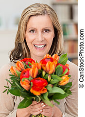 Happy smiling woman with a gift of flowers