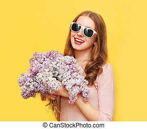 Happy smiling woman with bouquet of lilac flowers over yellow background