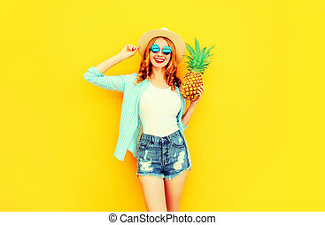 Happy smiling woman with pineapple having fun in summer straw hat, sunglasses, shorts on colorful yellow background