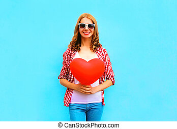 Happy smiling woman with red air balloon in the shape of a heart on blue background