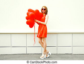 Happy smiling woman with red an air balloons in the shape of heart on a white background