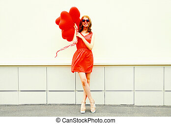 Happy smiling woman with red an air balloons in the shape of heart on white background