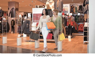 Happy smiling women coming out of the clothes store with bags. Friends girls go from entrance of luxury shop in mall after shopping. Slow motion.