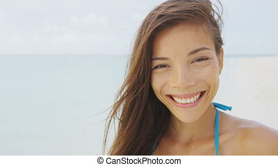 Happy smiling young Asian mixed race brunette woman on beach...
