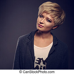 Happy smiling young blond woman with short bob hair style looking in grey trendy jacket on dark background. Closeup toned portrait