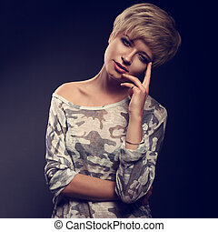 Happy smiling young blond woman with short bob hair style looking in grey trendy tunic on dark background. Closeup toned portrait