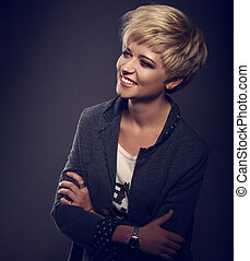 Happy smiling young business blond woman with short bob hair style looking in grey trendy jacket on dark background. Toned closeup portrait