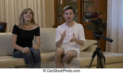Happy smiling young couple with camera recording video message for vlog at home on couch