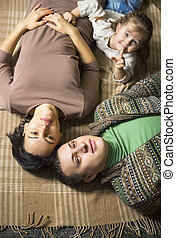 Happy smiling young family lying on the floor