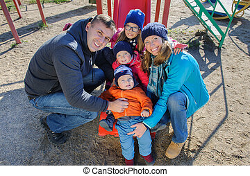 Happy smiling young family of five at children's playground in park