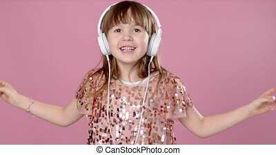 Happy smiling young girl dancing and singing in headphones. ...
