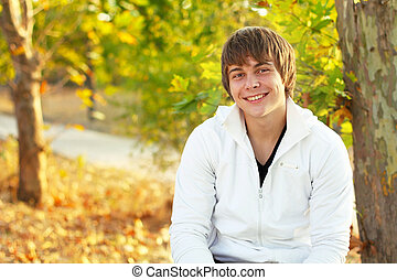 Happy smiling young man in autumn park outdoors