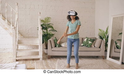 Happy smiling young mixed race girl getting experience using VR headset glasses of virtual reality and dancing at home