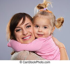 Happy smiling young mother hugs her little daughter